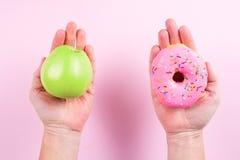Χέρια που επιλέγουν μεταξύ του μήλου και doughnut ως έννοια του healty τρόπου ζωής Στοκ εικόνες με δικαίωμα ελεύθερης χρήσης