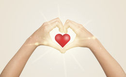 Χέρια που δημιουργούν μια μορφή με τη λάμποντας καρδιά Στοκ Φωτογραφίες