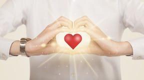 Χέρια που δημιουργούν μια μορφή με τη λάμποντας καρδιά Στοκ Εικόνες