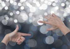 Χέρια που δημιουργούν την αόρατη μορφή ορθογωνίων με το λαμπιρίζοντας ελαφρύ υπόβαθρο bokeh Στοκ Εικόνες