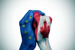 Χέρια που διαμορφώνονται τις ευρωπαϊκές και σημαίες του Καναδά που τίθενται με toget Στοκ εικόνα με δικαίωμα ελεύθερης χρήσης