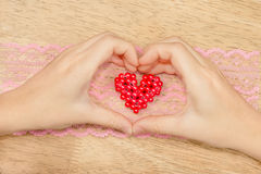 Χέρια που διαμορφώνουν μια καρδιά που παρουσιάζει μια καρδιά που διαμορφώνεται του κοκκίνου Στοκ φωτογραφία με δικαίωμα ελεύθερης χρήσης