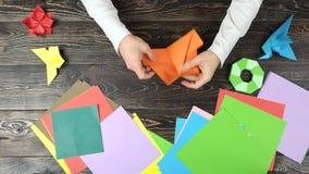 Χέρια που κάνουν τον αριθμό origami με το πορτοκαλί έγγραφο απόθεμα βίντεο