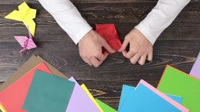 Χέρια που κάνουν το λουλούδι origami με το κόκκινο έγγραφο φιλμ μικρού μήκους