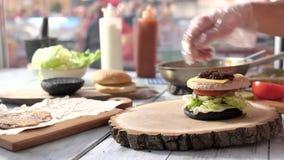 Χέρια που κατασκευάζουν το σάντουιτς γρήγορου φαγητού απόθεμα βίντεο