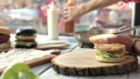 Χέρια που κατασκευάζουν burger απόθεμα βίντεο