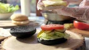 Χέρια που κατασκευάζουν cheeseburger απόθεμα βίντεο
