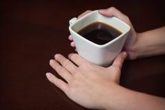 2 χέρια που κρατούν ένα θερμό φλιτζάνι του καφέ στοκ φωτογραφίες με δικαίωμα ελεύθερης χρήσης