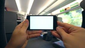 Χέρια που κρατούν ένα τηλέφωνο με μια άσπρη οθόνη στο τραίνο φιλμ μικρού μήκους