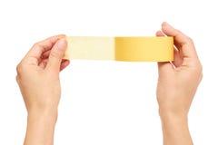 Χέρια που κρατούν μια κίτρινη κολλητική ταινία απομονωμένη στο άσπρο υπόβαθρο Στοκ φωτογραφία με δικαίωμα ελεύθερης χρήσης