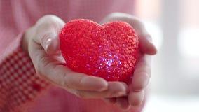Χέρια που κρατούν μια καρδιά ` s απόθεμα βίντεο