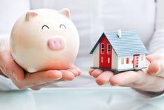 Χέρια που κρατούν μια piggy τράπεζα και ένα μοντέλο σπιτιών Στοκ εικόνες με δικαίωμα ελεύθερης χρήσης