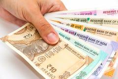 Χέρια που κρατούν ολοκαίνουργια 10, 50, 100, 200, 500 και 2000 ινδικά τραπεζογραμμάτια ρουπίων