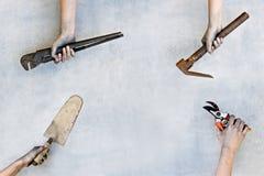 Χέρια που κρατούν τα εργαλεία κατασκευής στο γκρίζο υπόβαθρο στοκ φωτογραφίες