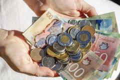 Χέρια που κρατούν τα καναδικά μετρητά και τα νομίσματα στοκ φωτογραφία