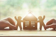 Χέρια που κρατούν τα ξύλινα άτομα και το σπίτι Σύμβολο της κατασκευής Στοκ φωτογραφία με δικαίωμα ελεύθερης χρήσης