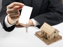 Χέρια που κρατούν την κενή επαγγελματική κάρτα με τα κλειδιά κτήμα έννοιας πραγματικό Στοκ φωτογραφία με δικαίωμα ελεύθερης χρήσης
