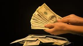 Χέρια που κρατούν τη δέσμη των δολαρίων, ξέπλυμα χρημάτων, παράνομη επιχείρηση, ανταπόδοση απόθεμα βίντεο