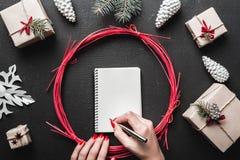 Χέρια που κρατούν τη μάνδρα και που γράφουν μια λίστα επιθυμητών στόχων επιστολών σε Άγιο Βασίλη με το διάστημα για το κείμενο Στοκ Εικόνα