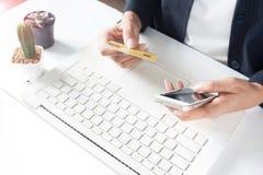 Χέρια που κρατούν τις πιστωτικές κάρτες, smartphone και που χρησιμοποιούν το lap-top Στοκ εικόνες με δικαίωμα ελεύθερης χρήσης