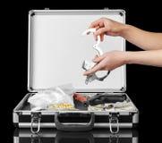 Χέρια που κρατούν τις χειροπέδες και τη βαλίτσα με τα φάρμακα, πυροβόλο όπλο στο Μαύρο Στοκ Φωτογραφία