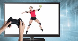 Χέρια που κρατούν τον ελεγκτή τυχερού παιχνιδιού με την πετοσφαίριση χάντμπολ στην τηλεόραση Στοκ Φωτογραφία
