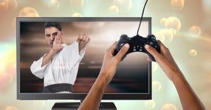 Χέρια που κρατούν τον ελεγκτή τυχερού παιχνιδιού με το φορέα μαχητών πολεμικών τεχνών στην τηλεόραση στοκ εικόνα