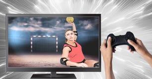 Χέρια που κρατούν τον ελεγκτή τυχερού παιχνιδιού με το φορέα χάντμπολ στην τηλεόραση Στοκ φωτογραφία με δικαίωμα ελεύθερης χρήσης