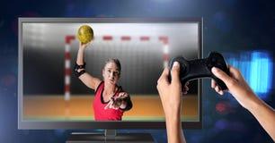Χέρια που κρατούν τον ελεγκτή τυχερού παιχνιδιού με το φορέα χάντμπολ στην τηλεόραση Στοκ Εικόνες