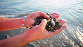 Χέρια που κρατούν τους βράχους παραλιών απόθεμα βίντεο