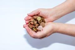 Χέρια που κρατούν το άσπρο υπόβαθρο νομισμάτων στοκ εικόνα