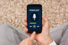 Χέρια που κρατούν το έξυπνο τηλέφωνο με την έννοια podcast στην οθόνη Στοκ φωτογραφία με δικαίωμα ελεύθερης χρήσης