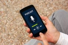 Χέρια που κρατούν το έξυπνο τηλέφωνο με την έννοια podcast στην οθόνη Στοκ Εικόνα