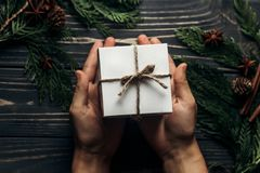 Χέρια που κρατούν το απλό παρόν κιβώτιο Χριστουγέννων και που δίνουν σε μοντέρνο στοκ εικόνες