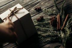 Χέρια που κρατούν το απλό παρόν κιβώτιο Χριστουγέννων και που δίνουν σε μοντέρνο Στοκ Φωτογραφία