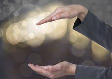 Χέρια που κρατούν το αόρατο διάστημα με το λαμπιρίζοντας ελαφρύ υπόβαθρο bokeh Στοκ φωτογραφία με δικαίωμα ελεύθερης χρήσης