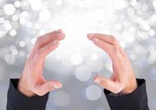 Χέρια που κρατούν το αόρατο διάστημα με το λαμπιρίζοντας ελαφρύ υπόβαθρο bokeh Στοκ Εικόνες