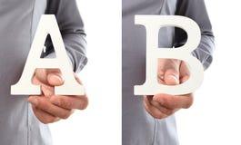 Χέρια που κρατούν το γράμμα Α και Β από το αλφάβητο που απομονώνεται σε ένα άσπρο β Στοκ Εικόνες