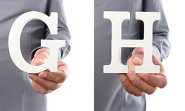 Χέρια που κρατούν το γράμμα Γ και Χ από το αλφάβητο που απομονώνεται σε ένα άσπρο β Στοκ Εικόνες