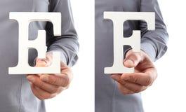 Χέρια που κρατούν το γράμμα Ε και Φ από το αλφάβητο που απομονώνεται σε ένα άσπρο β Στοκ Εικόνες