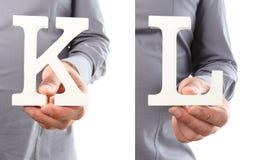 Χέρια που κρατούν το γράμμα Κ και Λ από το αλφάβητο που απομονώνεται σε ένα άσπρο β Στοκ Φωτογραφίες