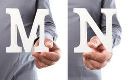 Χέρια που κρατούν το γράμμα Μ και Ν από το αλφάβητο που απομονώνεται σε ένα λευκό Στοκ φωτογραφία με δικαίωμα ελεύθερης χρήσης