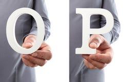Χέρια που κρατούν το γράμμα Ο και Π από το αλφάβητο που απομονώνεται σε ένα άσπρο β Στοκ Φωτογραφίες