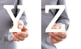 Χέρια που κρατούν το γράμμα Υ και Ζ από το αλφάβητο που απομονώνεται σε ένα άσπρο β Στοκ εικόνα με δικαίωμα ελεύθερης χρήσης
