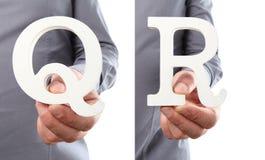 Χέρια που κρατούν το γράμμα Q και Ρ από το αλφάβητο που απομονώνεται σε ένα άσπρο β Στοκ Φωτογραφία