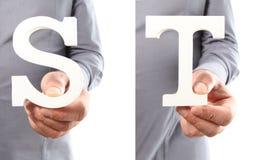 Χέρια που κρατούν το γράμμα S και Τ από το αλφάβητο που απομονώνεται σε ένα άσπρο β Στοκ φωτογραφία με δικαίωμα ελεύθερης χρήσης