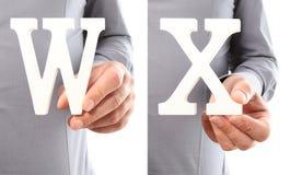 Χέρια που κρατούν το γράμμα W και Χ από το αλφάβητο που απομονώνεται σε ένα άσπρο β Στοκ εικόνα με δικαίωμα ελεύθερης χρήσης