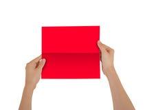 Χέρια που κρατούν το κενό κόκκινο βιβλιάριο φυλλάδιων στο χέρι Φυλλάδιο δημόσιες σχέσεις Στοκ Εικόνα