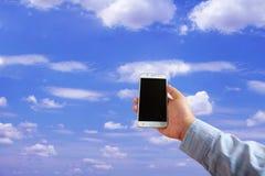 χέρια που κρατούν το κινητό τηλέφωνο στο μπλε ουρανό και το υπόβαθρο σύννεφων στοκ εικόνα με δικαίωμα ελεύθερης χρήσης