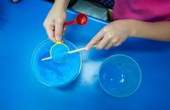 Χέρια που κρατούν το κουτάλι της μπλε χημικής ουσίας, θειικό άλας Pentahydra χαλκού Στοκ φωτογραφία με δικαίωμα ελεύθερης χρήσης